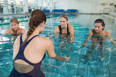 Female fitness class doing aqua aerobics on exercise bikes Royalty Free Stock Images