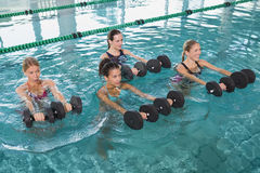 Female fitness class doing aqua aerobics with foam dumbbells. In swimming pool at the leisure centre Royalty Free Stock Images