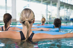 Female fitness class doing aqua aerobics with foam rollers Stock Photos