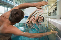 Female fitness class doing aqua aerobics with male instructor Royalty Free Stock Photos