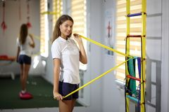 Beautiful, girl in the gym. A beautiful young girl is engaged in fitness with an expander. Stock Photo