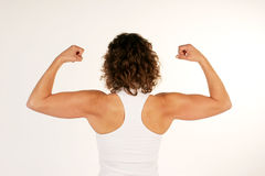 Female fitness instructor flexing arm muscles. A female fitness instructor flexing her back and arm muscles stock photo