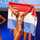 Female fitness model celebrates her victory on stage with flag Stock Image