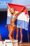 Female fitness model celebrates her victory on stage with flag Royalty Free Stock Images
