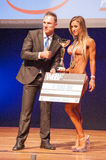 Female fitness model celebrates her victory on stage with offici Stock Photo