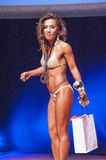 Female fitness model celebrates her victory on stage with offici Royalty Free Stock Image