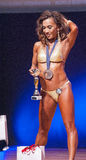 Female fitness model celebrates her victory on stage with offici Royalty Free Stock Photos