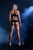 Female Fitness Model with dumbbells. Fitness female lifting dumbbells rear view on deep blue background with smoke Royalty Free Stock Images
