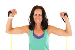 Female fitness model flexing muscles with stretch bands Stock Photography