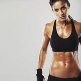 Female fitness model on grey background Royalty Free Stock Photo