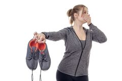 Smelly trainers after a long work out. Female fitness model holding up her smelly trainers Stock Photography