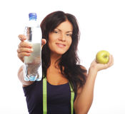 Female fitness model holding a water bottle and green apple Stock Photography