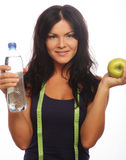 Female fitness model holding a water bottle and green apple Royalty Free Stock Photography