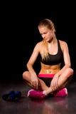 Female fitness model resting. Black background Stock Image