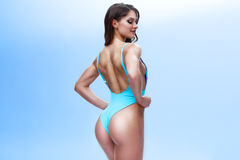 Female fitness model with a sporty body and long hair is posing in a light studio. Photo is made in a colourful and. Positive lifestyle royalty free stock photos