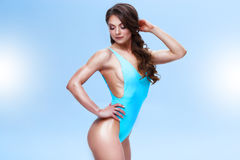 Female fitness model with a sporty body and long hair is posing in a light studio. Photo is made in a colourful and Royalty Free Stock Photo