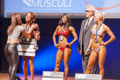 Female fitness models celebrate their victory on stage Stock Photos