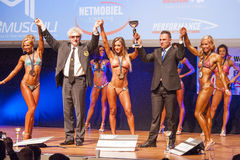 Female fitness models celebrate their victory on stage with offi Stock Images