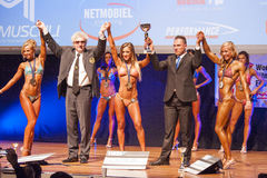 Female fitness models celebrate their victory on stage with offi Stock Photos
