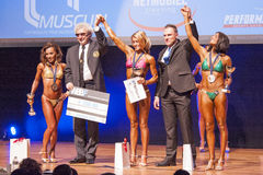 Female fitness models celebrate their victory on stage with offi Stock Image