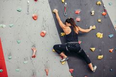 Young climber woman climbing on practical rock in climbing center, bouldering. Female fitness professional climber training at bouldering gym. Muscular woman royalty free stock images
