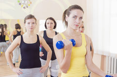 Female Fitness Teamwork Concepts. Closeup of Group of Four Caucasian Female Athletes Exercising with Barbells Stock Photos