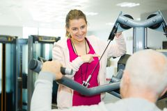 Female fitness trainer helping senior on in fitness center. Female fitness trainer helping senior on in a fitness center Royalty Free Stock Image