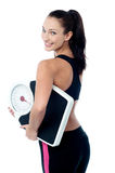 Female fitness trainer holding weighing machine Royalty Free Stock Images