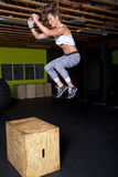 Female Fitness Trainer Jumps Onto Box Stock Image