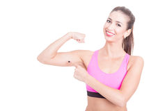 Female fitness trainer showing her biceps and smiling Royalty Free Stock Photos