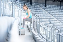 Female fitness trainer working out on stairs, preparing for training - stretching and doing squats Royalty Free Stock Photos