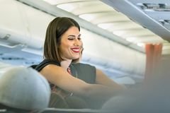 A female flight attendant of Aegean Airlines serving a passenger smiling stock images