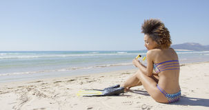 Female with flippers sitting on beach Stock Image