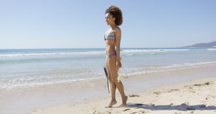 Female with flippers standing on beach Royalty Free Stock Photography