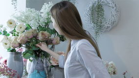 Female florist arranges flowers in vases at flower shop. Side view of a young attractive florist arranging flowers in vases at the flower shop. Young caucasian stock footage