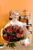 Female florist with bouquet of flowers, smiling, portrait Royalty Free Stock Photos