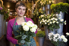 Female florist with bunch of roses, smiling, portrait Stock Photo