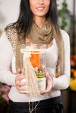 Female florist with candle in flower shop. Female florist in flower shop or nursery with candle in glass Stock Photography