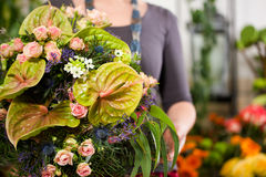 Female florist in flower shop. Or nursery presenting her plants on display Stock Images