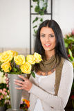 Female florist in flower shop. Or nursery presenting yellow roses Royalty Free Stock Images
