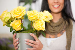 Female florist in flower shop. Or nursery presenting yellow roses Stock Images
