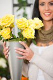 Female florist in flower shop. Or nursery presenting yellow roses Stock Photography