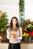 Female florist in flower shop. Or nursery with candle in glass Royalty Free Stock Photography