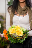 Female florist in flower shop. Or nursery presenting her plants on display Stock Photo