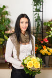 Female florist in flower shop. Or nursery with yellow roses Stock Photo