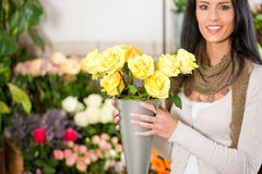 Female florist in flower shop. Or nursery presenting yellow roses Royalty Free Stock Image