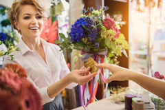 Female florist getting credit card for bouquet Royalty Free Stock Photo