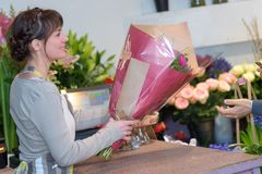 Female florist giving bouquet to client royalty free stock photography