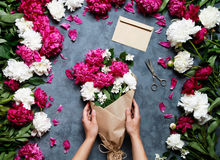 Female florist holding beautiful bouquet at flower shop. Florist at work: pretty woman making summer bouquet of peonies Stock Photography