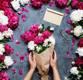 Female florist holding beautiful bouquet at flower shop. Florist at work: pretty woman making summer bouquet of peonies Royalty Free Stock Photography